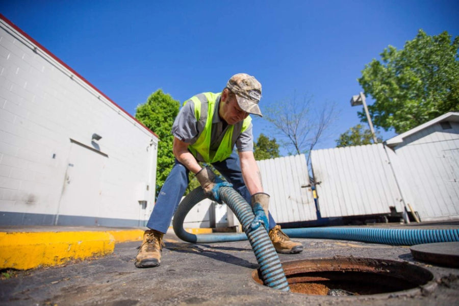 Service man doing grease trap pumping